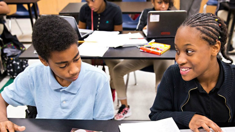 A smiling girl looks at a boy who is reviewing a paper on a school desk in an education setting that uses data