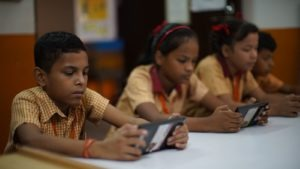 A young man in India completes schoolwork using an electronic device.