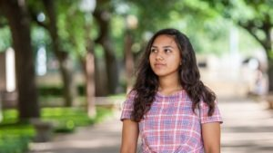 A future physician walks on the campus of UT Austin after attending Dell Medical School's Health Sciences Summer Camps