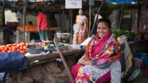 A Svasti customer sits in front of her vegetable stall in an Indian market.