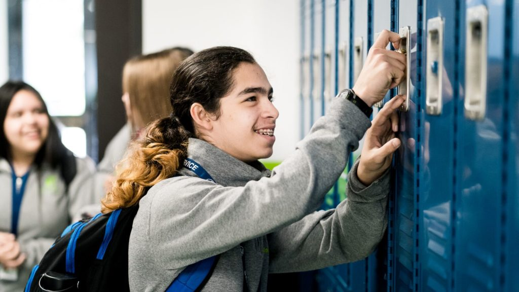 A young man opens his locker