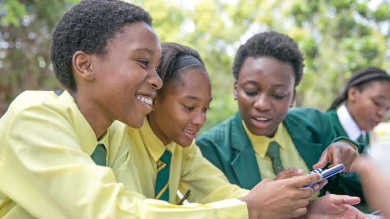 Three South African students work on Siyuvula math assignments using a phone